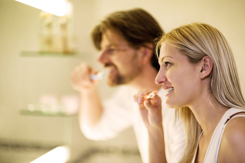 A ,  couple brushing their teeth as part of their periodontal health