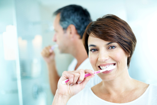 a dental implant patient from Sussex Dental brushing her teeth